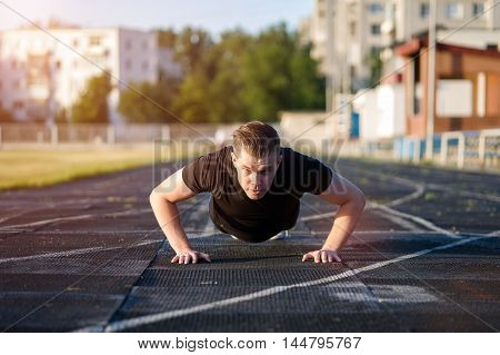Strong healthy man doing push ups outdoors, fitness workout