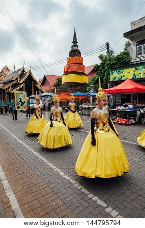 CHIANG MAI THAILAND - AUGUST 24: Young girls in festival costumes parade near the ancient temple on August 24 2016 in Chiang Mai Thailand.