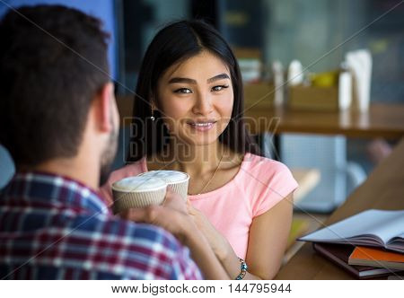 Picture of romantic couple having date. People drinking coffee and sitting face to face. Korean or Asian lady smiling for camera.