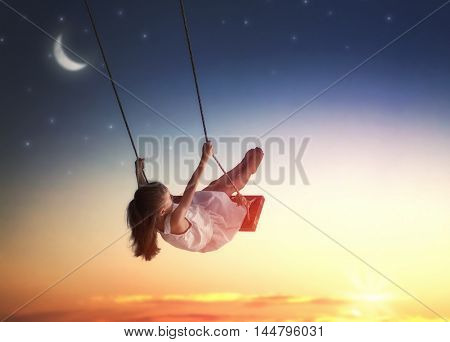 Happy child girl on swing in sunset summer