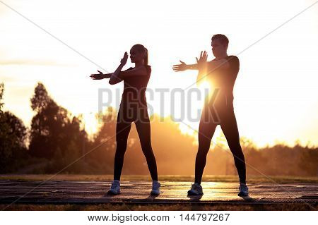 Two silhouettes of young healthy man and woman exercising at sunset. Fitness or running workout outdoors