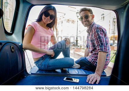 Happy tourist man and woman in sunglasses looking at camera while sitting in car. Female and male travelling all over world.