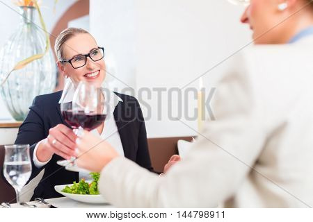 Women on business lunch toasting with wine to celebrate an agreement