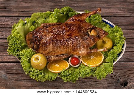 Baked young duck with apples and green lettuce on the wooden surface