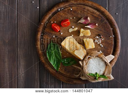 Cheese delikatessen closeup on rustic wood. Wooden desk with parmesan, camembert and brie cuts decorated with garlic, tomato and basil, top view image with copy space