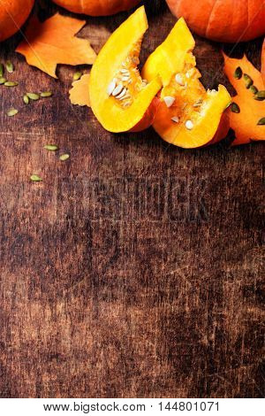 Pumpkins pieces. Frame with pumpkins on a wooden table with copyspace.
