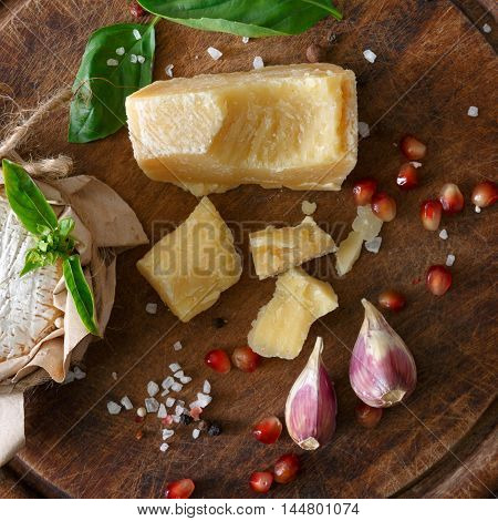 Cheese delikatessen closeup on rustic wood. Wooden desk with parmesan, camembert and brie cuts decorated with garlic, pomegranate and rosemary, top view image