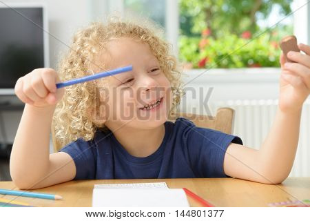 a little blond boy drawing in his home