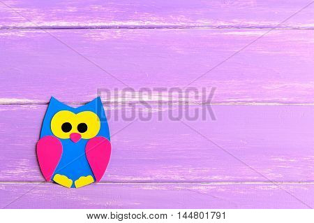 Cute paper owl isolated on a bright wooden background with blank space for text. Children paper crafts. Children art in kindergarten and at home. Kids background