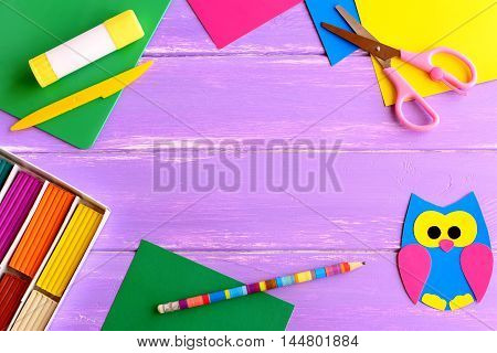 Paper owl, plasticine set, color paper sheets, scissors, glue stick, pencil on wooden background with empty place for text. Back to school background for kids, students. School stationery