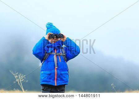 kids travel - little boy with binoculars hiking in winter mountains