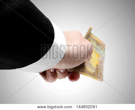Man's hand holding a stack of fifty euro notes.