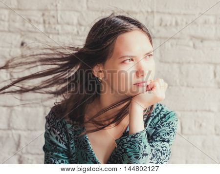Stern and serious looking away young brunette beauty. Closeup portrait of serious young woman with sensual look away. Girl rests her chin on hand and serious looking away