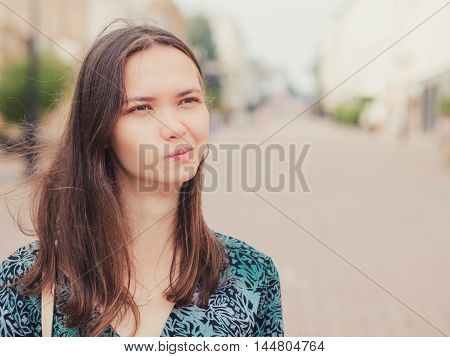 displeased handsome young woman looking away outdoors with copy space