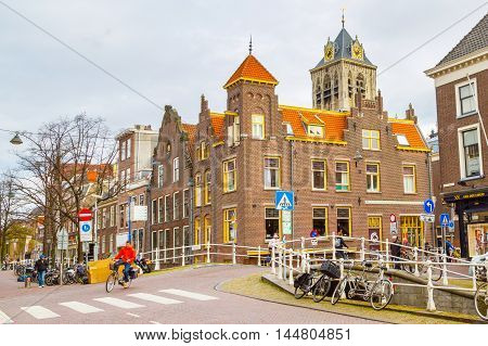 Hague, Netherlands - April 6, 2016: Street view with traditional dutch houses, clock tower, people and bicycles in Hague, Holland