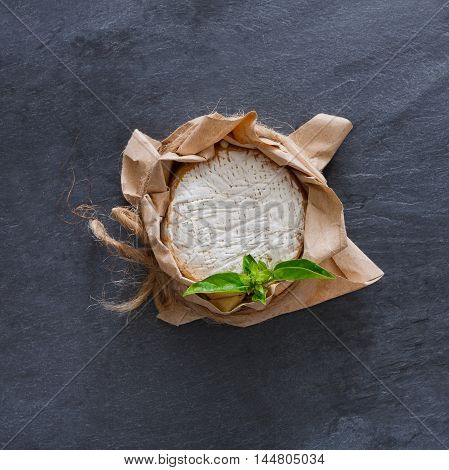 Cheese delikatessen closeup on black stone surface. Camembert or brie circle in brown kraft paper decorated with basil, top view image