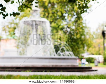 blurred of fountain and green foliage, out of focus image. Fountain and green trees as background