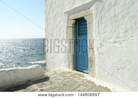 The entrance to one of the five churches that form The Church Mykonos, Greece - A blue door on a whitewashed wall. The entrance to one of the five churches that form The Church of Panagia Paraportiani.