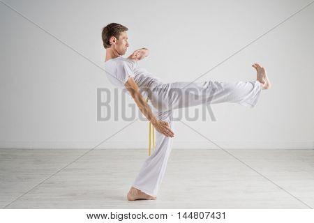 Man in sportswear performing a kick.