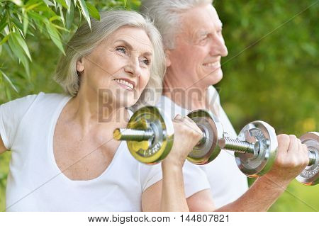 Happy fit senior couple exercising with dumbbells in  park