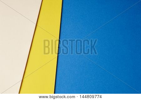 Colored cardboards background in beige yellow blue tone. Copy space. Horizontal