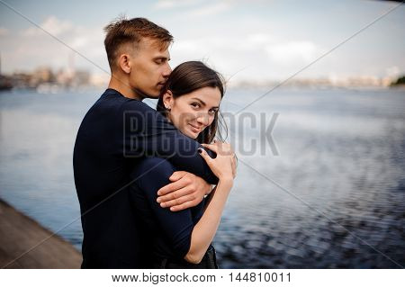 Attractive happy couple cuddling at the beach