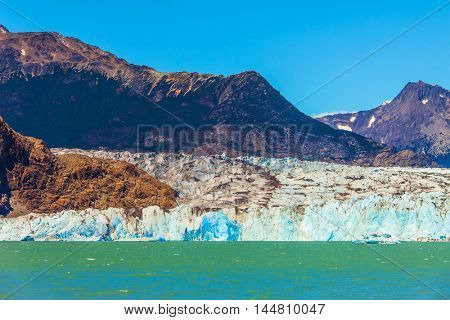 Massive glacier descends into the emerald water. In the water ice-floes, broken away from a glacier. The picturesque multi-colored shore of Lake Viedma