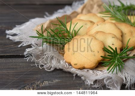 Delicious freshly baked homemade cookies with rosemary on a wooden surface, rustic style, selective focus