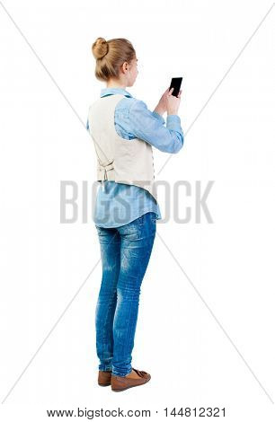 back view of standing young beautiful  woman  in vest and using a mobile phone. girl  watching. Rear view people collection.  backside view of person.  Isolated over white background. Girl in