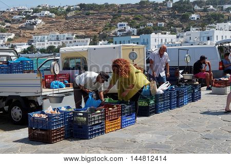 Mykonos, Greece - August 13 2016: Local vendors sell products at the coastline. Every morning local vendors sell fruits, vegetables or fishes at the coastline of Mykonos Town (Chora).