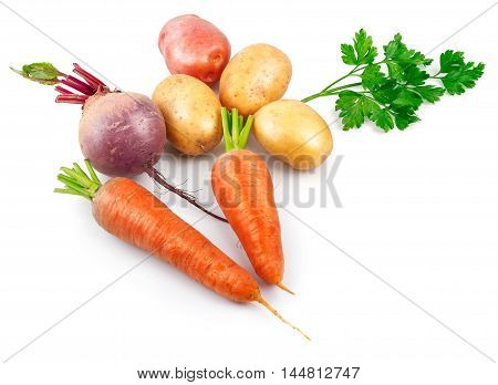 Organic vegan food still life harvest of fresh ripe vegetables. Potatoes, carrots, beet and parsley, isolated on white background