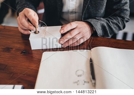 Closeup of an entrepreneur sitting at a table stamping a seal on a package for delivery with a open notebook beside him