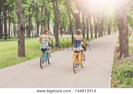 Happy boho chic stylish girls ride away together having fun. Beautiful women on bicycles with baskets full of wild flowers. Female friends, youth and happiness, active summer leisure in park concept.