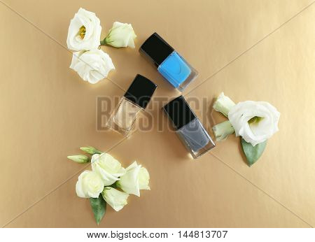 Nail polish and flowers on beige background