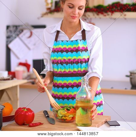 Young woman mixing fresh salad standing near desk .