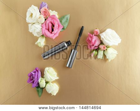 Mascara and flowers on beige background