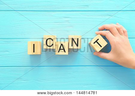Phrase I CANT transforming into CANT on wooden background