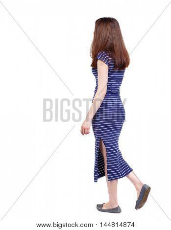 back view of walking woman. brunette in a blue striped dress goes sideways.