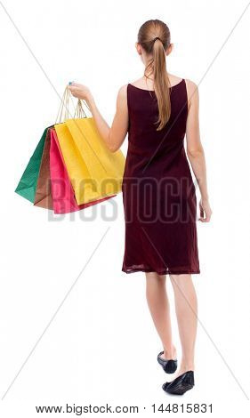 back view of going woman with shopping bags Isolated over white background. The girl in the maroon sleeveless dress holding shopping bags.
