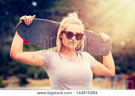 Pretty blond girl holding skateboard