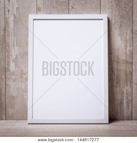 Blank white picture frame on the wall and the floor