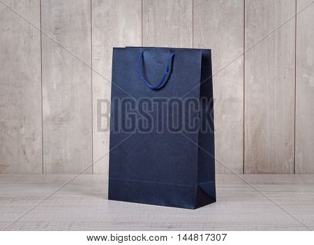 Paper shopping bag on wooden table