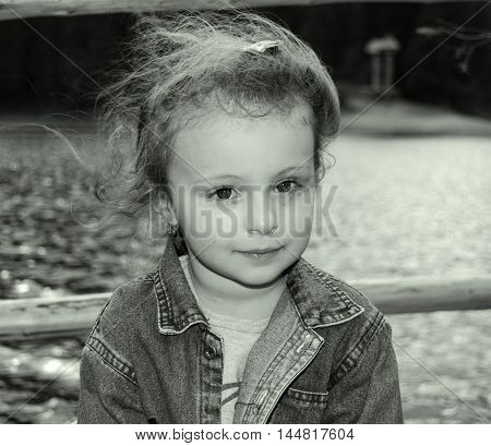 Lake Synevir - SEPTEMBER 16:Black and white photo of a little girl on a background of lake Synevir. Children. Nature. September 16, 2015 in the lake Synevir, Ukraine.