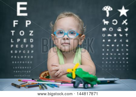 Kid in glasses for sight sitting at a table against the background of the school boards and tables for inspection of