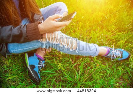 Young girl in leather jacket and ripped jeans sitting on the grass in the park and talking to friends on the phone.