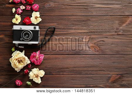 Beautiful composition of vintage camera and colourful flowers on wooden  background