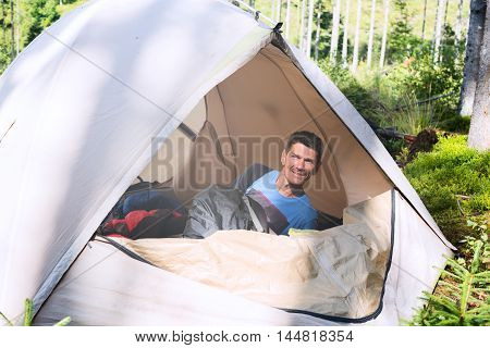 Adult hiker woke up and looks at the sun out of the tent enjoying life