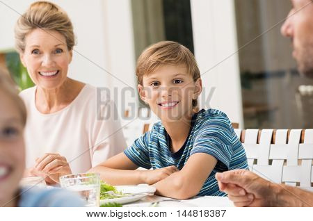Boy enjoying lunch with grandparents. Family eating together for lunch. Portrait of happy smiling grandchild looking at camera during meal.