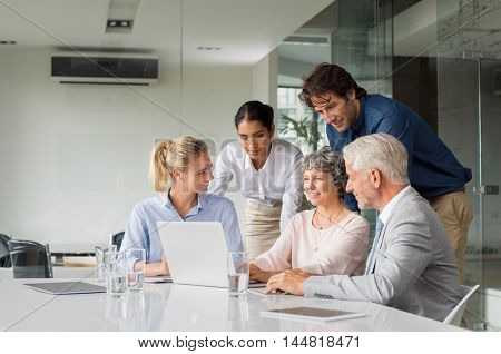 Business people having meeting around table in modern office. Group of businessmen and businesswomen working together on computer. Senior businesswoman showing marketing strategy to team on laptop.