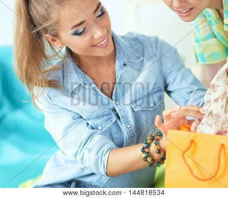 Two young women sitting with shopping bag at home